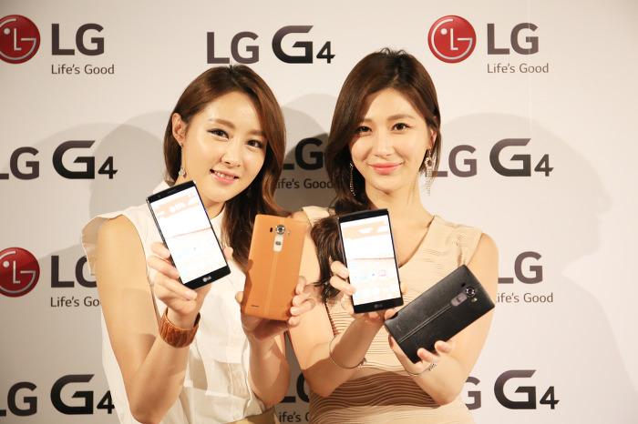 모델들이 LG G4 스마트폰을 들고 포토월 앞에 서 있다.