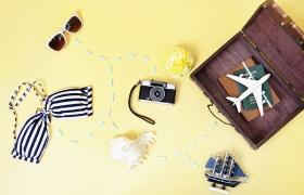 열려있는 여행 가방 안에 비행기와 여권이 보인다. 그 외 카메라, 수영복, 선글라스 등이 놓여있다.