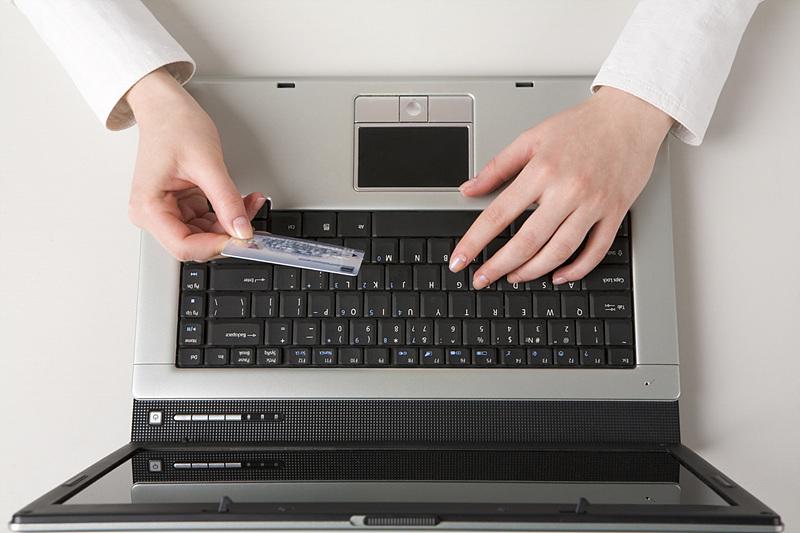 노트북을 켠 채 신용카드 번호를 입력하고 있는 이미지