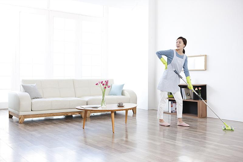 한 여성이 거실을 밀걸레로 닦고 있는 모습
