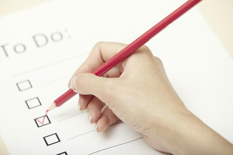 빨간색 펜으로 체크 리스트를 표기하는 모습
