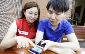 LG전자 임직원봉사단이 시각장애인에게 '책 읽어주는 폰' 사용법을 설명하는 모습입니다.