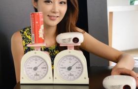 모델이 저울로 콜라 캔과 미니빔의 무게를 비교하고 있습니다.