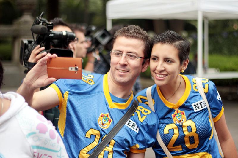 파란색 유니폼을 맞춰 입은 두 사람이 함께 셀피를 촬영하고 있다.