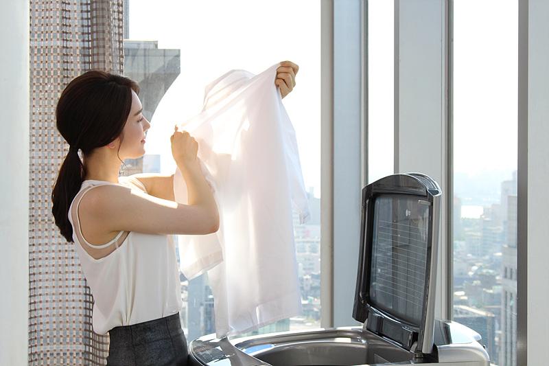 모델이 통돌이 세탁기에서 셔츠를 꺼내 햇빛에 비춰보고 있는 모습