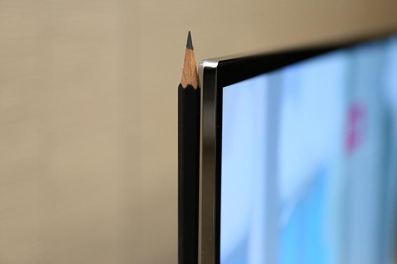 LG OLED UHD TV 옆에 깎아놓은 연필을 대고 있는 모습
