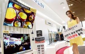 모델이 매장에서 LG 올레드 TV를 소개하고 있습니다.