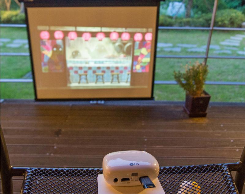 야외에서 LG 미니빔 TV를 작동시키고 있는 모습. 스크린에 화면이 선명하게 보인다.