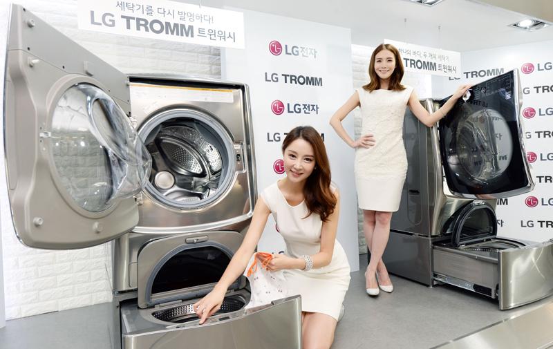 LG 트롬워시 앞에 두 명의 모델이 포즈를 취하며 서 있다.