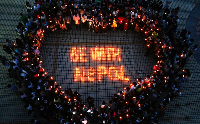 촛불로 하트를 만든 사람들. BE WITH NEPAL 이라는 문구가 가운데 촛불로 밝혀져 있다.