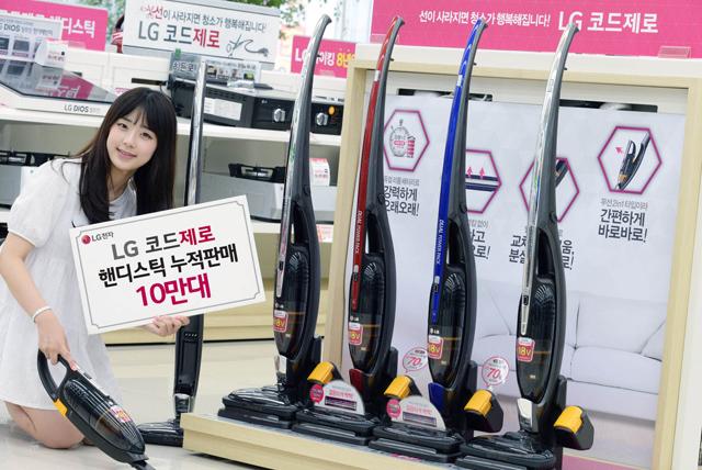 모델이 LG 베스트샵 매장에서 '코드제로 핸디스틱' 청소기를 소개하고 있습니다.