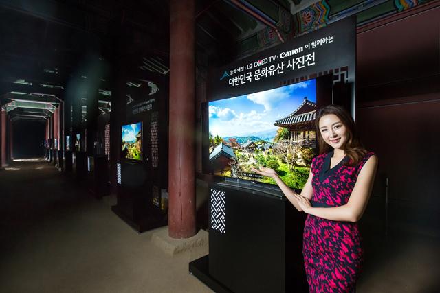 모델이 경복궁에서 압도적 화질의 올레드 TV를 통해 우리 문화유산을 전시하는 대한민국 문화유산 전시회를 소개하고 있습니다.