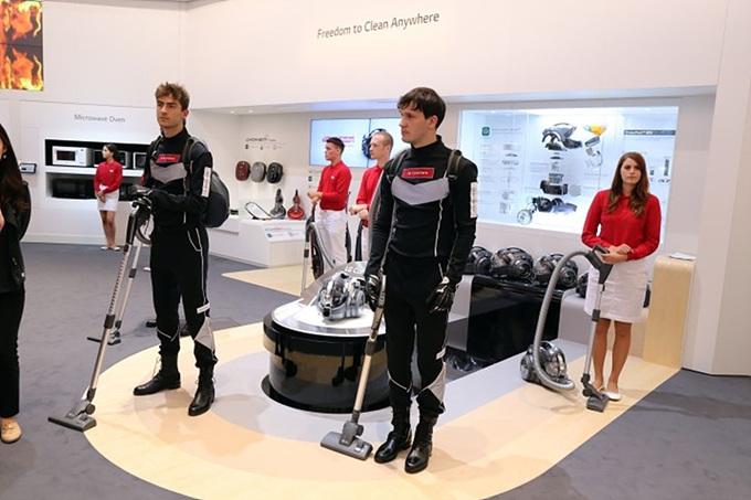 코드제로 제품을 손에 들고 검은색 유니폼을 입고 있는 코드제로맨과 부스 도우미들