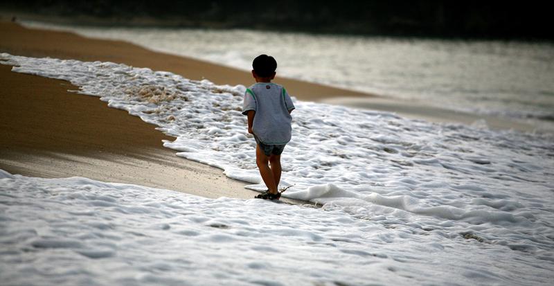 바닷가에서 파도와 함께 노는 아이