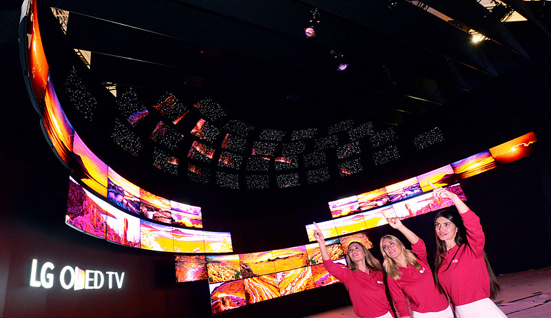 IFA 2015 부스 전경. 모델들이 전시된 OLED TV를 가리키고 있다.