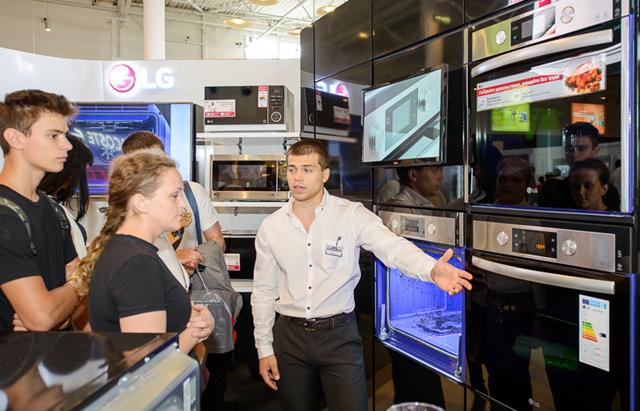 고객들이 빌트인 오븐을 살펴보고 있습니다.