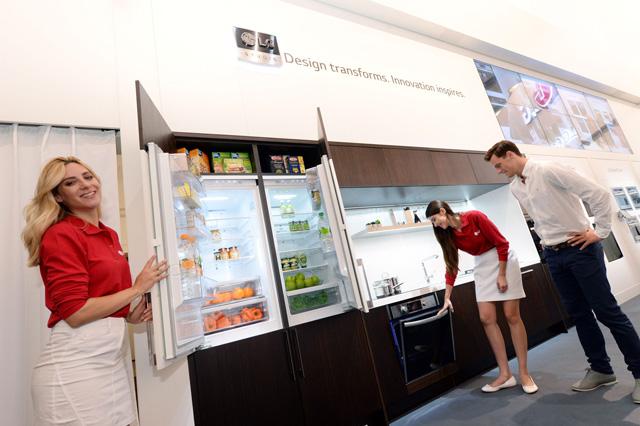 모델이 빌트인 오븐, 빌트인 냉장고 등을 소개하고 있습니다.