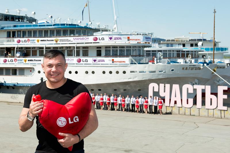 빨간색 LG 로고개 새겨진 하트 모양 쿠션을 안고 있는 러시아 스포츠 선수