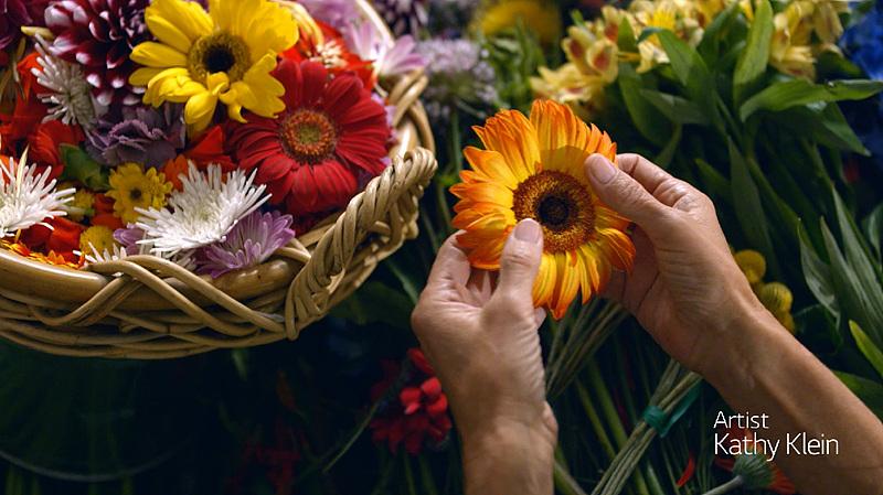 캐시 클라인이 작품의 재료가 되는 꽃을 손으로 들고 있다.