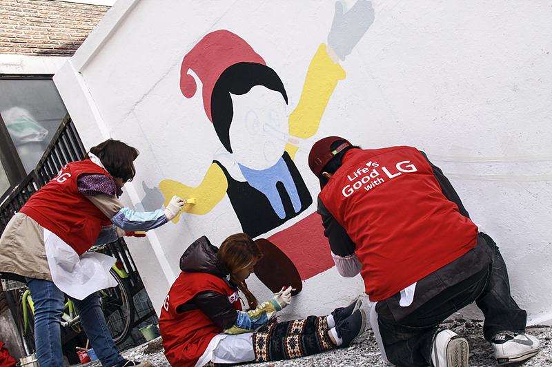벽화를 그리고 있는 Life's Good 자원봉사단의 모습