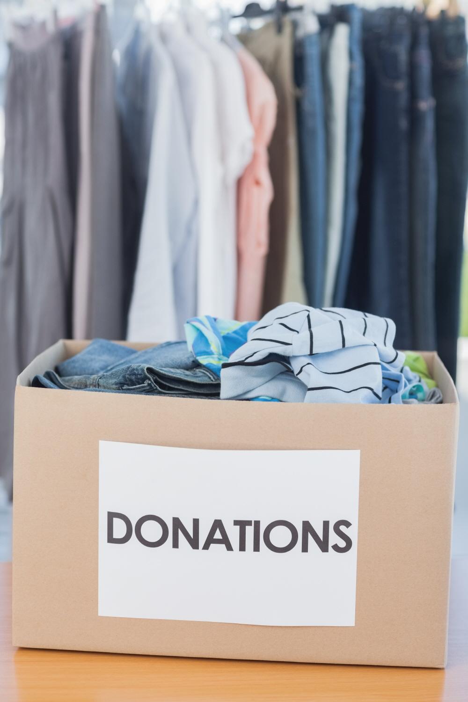 Donations 문구가 적혀 있는 상자 안에 옷이 가득 담겨 있다