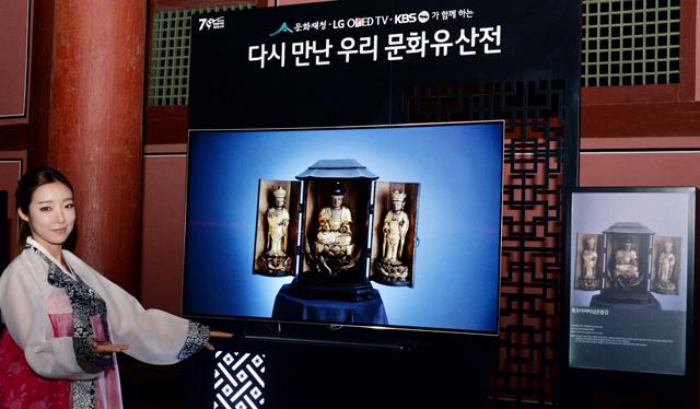 모델이 경복궁 근정전 회랑에서 올레드 TV를 통해 일본 고려박물관에 전시된 목조아미타삼존불감을 소개하고 있습니다.