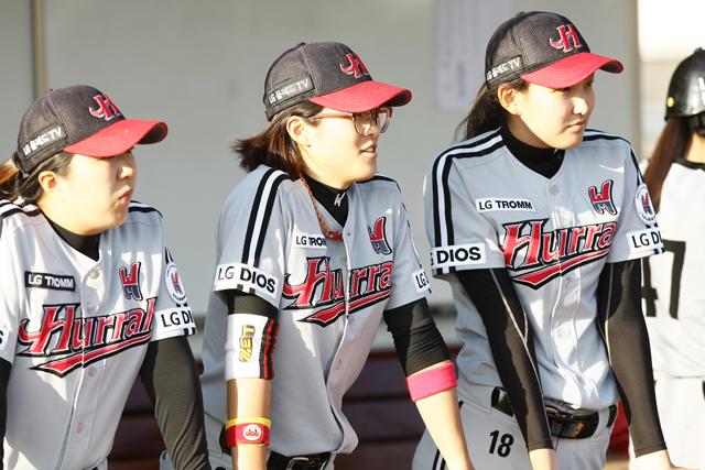 여자 야구선수 세명이 경기모습을 지켜보고 있다
