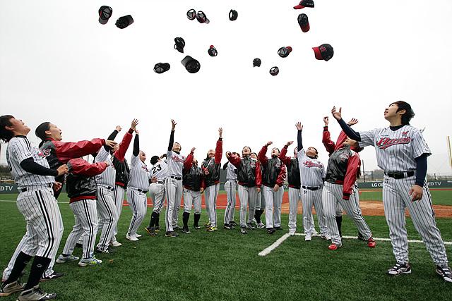 선수들이 동드랗게 서서 모자를 하늘위로 던지는 모습
