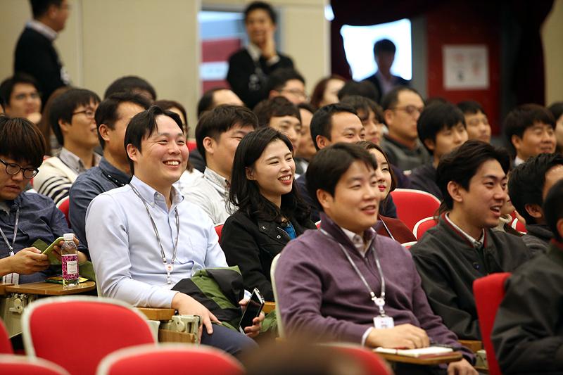 청중이 웃으며 발표를 듣는 모습