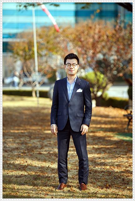 짙은 네이비 색상의 체크무늬 수트에 하늘색 셔츠를 입은 김병록 연구원의 모습