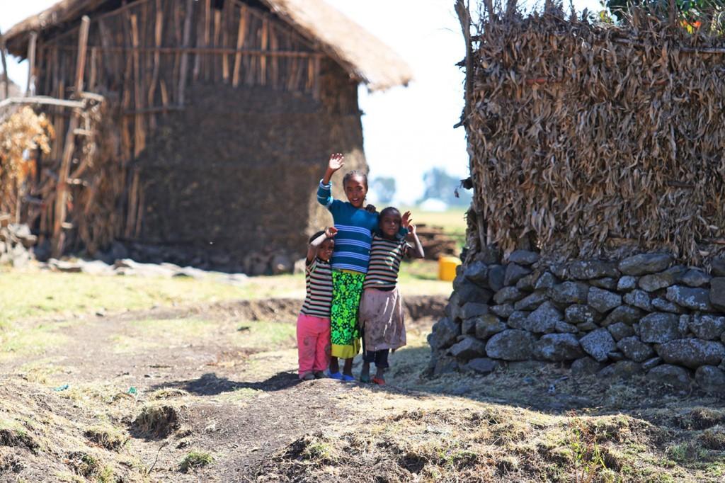 에티오피아 아이 셋이 카메라를 향해 손을 흔들고 있다
