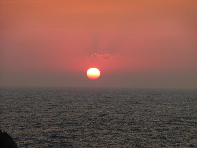 수평선 위로 빨간 태양이 지는 모습