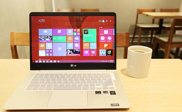 카페 테이블에 LG 노트북과 커피가 놓여져 있는 모습