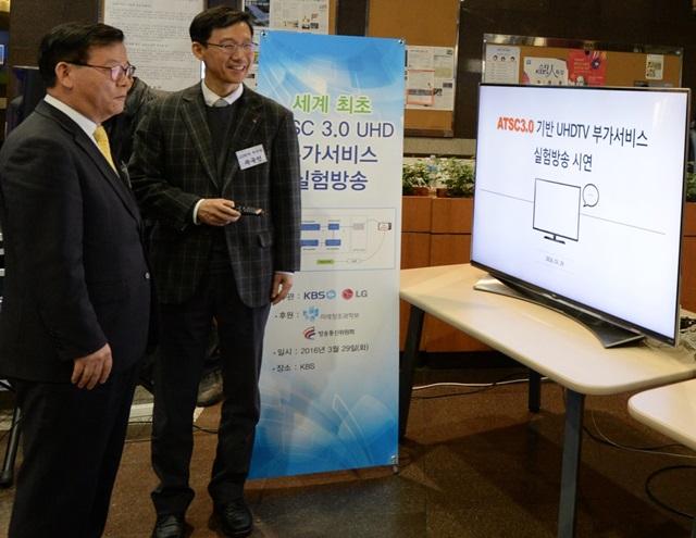 : LG전자 차세대 표준연구소장 곽국연 부사장(오른쪽)과 KBS 박병열 기술본부장(왼쪽)이 ATSC 3.0기반의 울트라HD 부가서비스를 시연하고 있다.