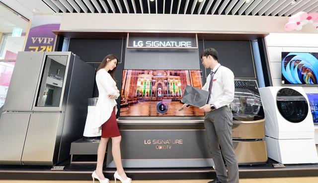 LGE_시그니처 체험존_01~03: LG베스트샵 불광본점에서 직원이 매장을 찾은 고객에게 초프리미엄 가전 제품인 'LG 시그니처'를 소개하고 있다.