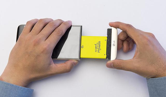손으로 LG G5 모듈형 배터리를 빼내고 있는 모습
