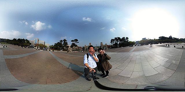 넓은 광장에서 LG 프렌즈 360 캠을 이용해 셀카 촬영하는 모습