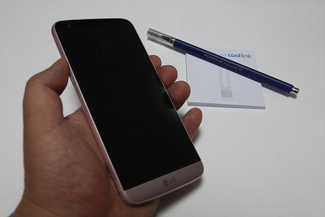 LG G5가 손에 들려 있고, 펜과 포스티잇이 탁자 위에 놓여 있습니다.