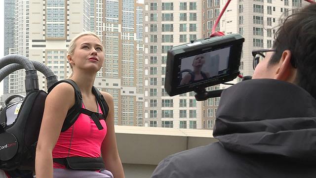 시에라 블레어 코일이 고층 빌딩을 바라보고 있는 모습을 촬영하는 카메라 맨