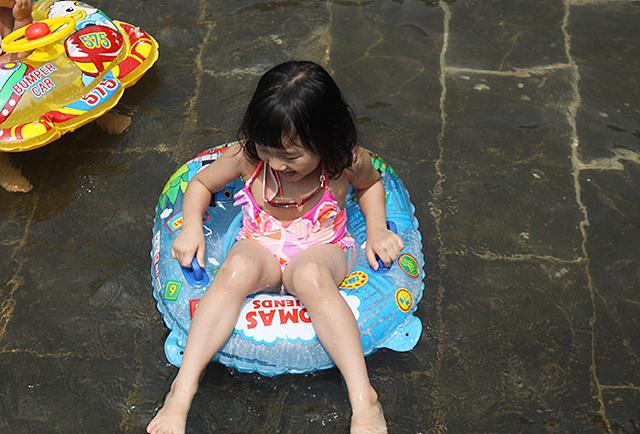 튜브에 타고 물놀이를 즐기는 여자 아이의 모습