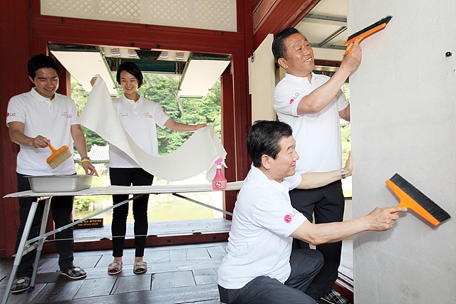 LG전자 임직원들이 창덕궁에서 벽지를 바르고 있는 모습
