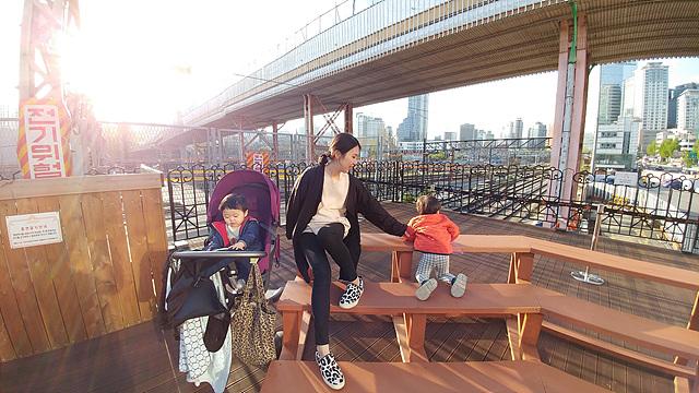 엄마와 아이 둘이 야외 벤치에 있는 모습입니다.