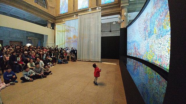 사람들이 넓은 모니터 화면을 보고 있는 모습을 G5로 촬영한 사진입니다.