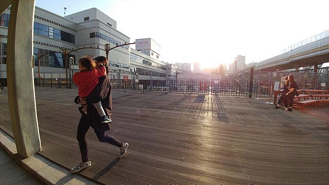야외에서 아이를 안고 걸어가는 여성의 모습을 G5로 촬영한 사진입니다.