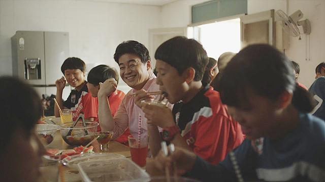 깜짝 방문한 백종원씨와 강경여자중학교 축구부 학생들이 간식 먹고 있는 모습