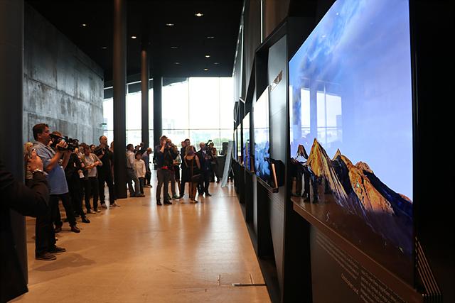 사진전 관람객들이 LG 올레드 TV를 통해 아이슬란드 대자연의 모습을 보고 있습니다.