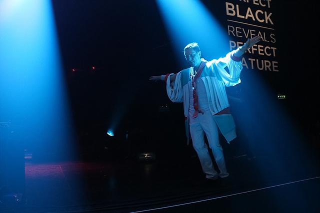 한 아티스트가 팔을 벌리고 무대 위에 서있습니다.