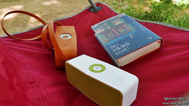 캠핑 의자 위에 올려져 있는 LG 포터블스피커 2대와 책