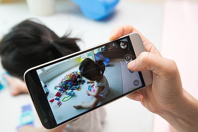 스마트폰으로 아이가 놀고 있는 모습을 촬영하는 사진