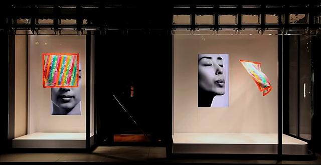 에르메스 매장 내 스카프 전시 관련 사진으로, 디지털 사이니지 속에 여성이 바람을 불면 스카프가 날리면서 입체적인 효과를 보여주고 있습니다.